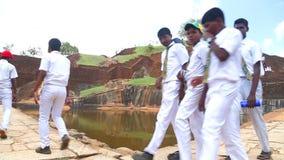SIGIRIYA, SRI LANKA - FEBRUAR 2014: Schuljungen, die vorbei auf die Oberseite der Felsen-Festung in Sigiriya, ein alter Palast ge stock video
