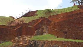 SIGIRIYA, SRI LANKA - FEBRUAR 2014: Schuljungen, die vorbei auf die Oberseite der Felsen-Festung in Sigiriya, ein alter Palast ge stock footage