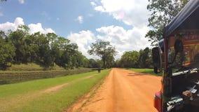 SIGIRIYA, SRI LANKA - MÄRZ 2014: Ansicht vom tuktuk, das auf Sandbahn im Park von Sigiriya-Felsen fährt stock video