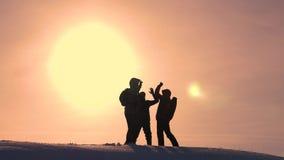 Οι τουρίστες έρχονται να ολοκληρώσουν του χιονώδους λόφου και να χαρούν για τη νίκη ενάντια στο σκηνικό ενός κίτρινου ηλιοβασιλέμ στοκ εικόνα με δικαίωμα ελεύθερης χρήσης