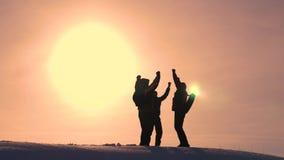 Οι τουρίστες έρχονται να ολοκληρώσουν του χιονώδους λόφου και να χαρούν για τη νίκη ενάντια στο σκηνικό ενός κίτρινου ηλιοβασιλέμ στοκ εικόνες