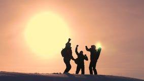 Οι τουρίστες έρχονται να ολοκληρώσουν του χιονώδους λόφου και να χαρούν για τη νίκη ενάντια στο σκηνικό ενός κίτρινου ηλιοβασιλέμ στοκ φωτογραφία