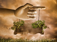 Sign. A wooden hand pointing with a wooden sign hanging from chains and wrapped with a vine Stock Images