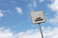 Sign. Swimming permitted between yellow flags only. Information sign against the cloudy sky Stock Images