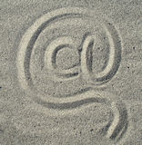 At sign. Manually at sign on sand Royalty Free Stock Photo