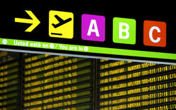 Sign at airport. Showing the route to the gates.With Spanish and English text.At background arrival and departure board Stock Photography