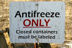 Sign Antifreeze Only. An old cracked and stained white dump sign that reads Antifreeze Only. Could be used for background texture, pollution problem or concerns Stock Photo