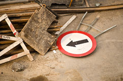 Sign with arrow. Cluttered objects thrown on the street Stock Photography
