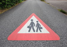 Sign on asphalt road with school or working person Royalty Free Stock Photos