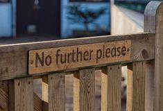"""No further please"" Sign on wooden gate. Wisley, Surrey. A polite request attached to wooden gate by screws, telling people No further please. Could royalty free stock photo"