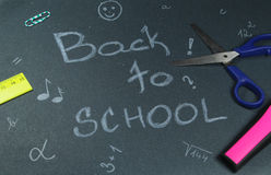 Sign ,,Back to school` on black background. This is notice ,,Back to school` on black background with school aids Stock Images