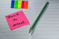 Sign ,,Back to school` on exercise book. This is notice ,,Back to school` on white exercise book with school aids Stock Images