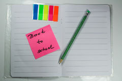 Sign ,,Back to school` on exercise book. This is notice ,,Back to school` on white exercise book with school aids Royalty Free Stock Photo