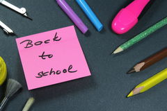 Sign ,,Back to school` on sticker and school aid. This is notice ,,Back to school` on black background with school aid Royalty Free Stock Photography
