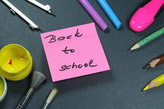 Sign ,,Back to school` on sticker and school aid. This is notice ,,Back to school` on black background with school aid Stock Images