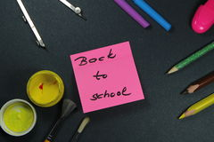 Sign ,,Back to school` on sticker and school aid. This is notice ,,Back to school` on black background with school aid Stock Photo