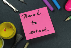 Sign ,,Back to school` on sticker and school aid. Royalty Free Stock Photo