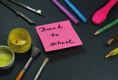 Sign ,,Back to school` on sticker and school aid. This is notice ,,Back to school` on black background with school aid Royalty Free Stock Images