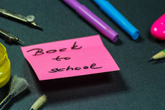 Sign ,,Back to school` on sticker and school aid. This is notice ,,Back to school` on black background with school aid Royalty Free Stock Photos