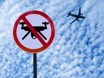 Sign ban drones on sky background with clouds and taking off plane. Round sign ban drones on sky background with clouds and taking off plane stock photos