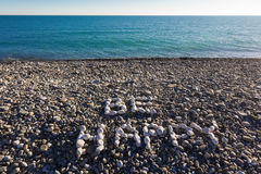 The sign be happy made from white pebbles. On pebble beach on the sea Royalty Free Stock Image