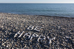 The sign Be Happy made from white pebbles on pebble beach on the. Sea Royalty Free Stock Photos