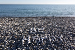 The sign Be Happy made from white pebbles on pebble beach on the. Sea Royalty Free Stock Photography