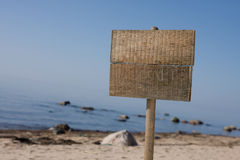 Sign at beach. One blank wooden sign at empty beach Royalty Free Stock Photo