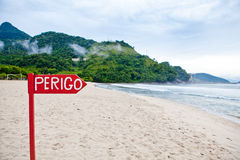 The sign on the beach. The sandy beach at the blue sea with beautiful mountains in the background Stock Photos