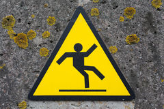 Sign beware slippy on wall Stock Images