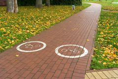 Sign of the bicycle zone. On the paved path on cloudy day Royalty Free Stock Images