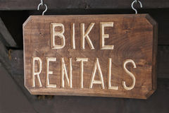 Sign `bike rentals` on a wooden plate Stock Photos