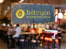 Sign bitcoin accepted here hanging in front of restaurant door. Bitcoin , electronic money concept royalty free stock photos