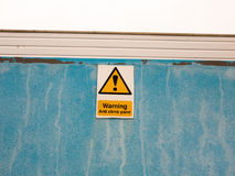 A sign on blue wall saying warning anti climb paint Royalty Free Stock Photo