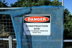 Sign board `Danger Construction Site Unauthorised persons keep out`. Sign board `Danger Construction Site Unauthorized persons keep out` at a construction site Stock Images