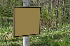 Sign board in the forest - customizable. Worn out sign board in the woods. Empty canvas for customization. Concept of forestry development and education. Banner Royalty Free Stock Photography