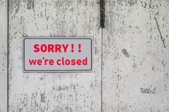 Sorry we are closed sign hang on door of business shop. A Sign board of sorry we are closed hang on door of business shop with nature green background stock photos