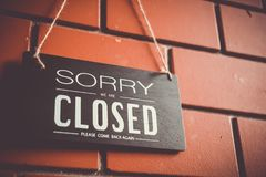 Sorry we are closed sign hang on door of business. A Sign board of sorry we are closed hang on door of business shop with nature green background royalty free stock images
