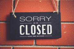 Sorry we are closed sign hang on door of business shop. A Sign board of sorry we are closed hang on door of business shop with nature green background royalty free stock image
