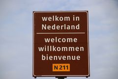 Sign on the border in 4 languages to welcome travelers in the Netherlands at the ferry of Hoek van Holland. Sign on the border in 4 languages to welcome stock image