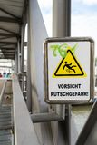 Sign on a bridge warning against slipping royalty free stock photography