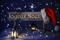Sign Candlelight Santa Hat Joyeux Noel Means Merry Christmas. Wooden Christmas Sign And Santa Hat With Snow. French Text Joyeux Noel Means Merry Christmas For Stock Photos