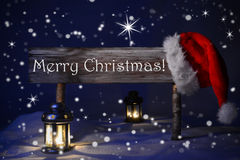 Sign Candlelight Santa Hat Merry Christmas. Wooden Christmas Sign And Santa Hat With Snow In Snowy Scenery. English Text Merry Christmas For Seasons Greetings Stock Images