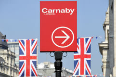 Sign for Carnaby Street London. Direction sign for Carnaby Street London and Union Jack flags Stock Photos