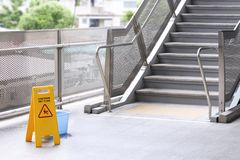 Free Sign Caution Warning Floor Wet And Cleaner Equipment On The Stair In Skytrain Station. Safety Sign With Text Caution Stock Photography - 155944522