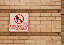 Sign on brick wall in city of Chicago saying Curb Your Dog Stock Photography