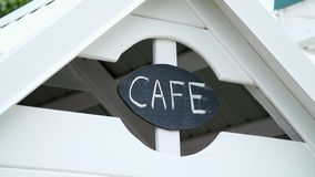 A sign on a children`s play house, an inscription of a cafe, on a black board written in white chalk word-cafe stock video footage