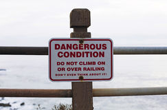 Sign on coastline to be aware of danger Stock Photography