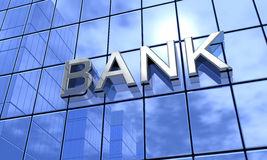 Sign on commercial bank. Sunlight and skyscrapers reflecting on blue glass windows of commercial building with bank sign Royalty Free Stock Image