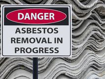 Sign danger asbestos removal in progress and a stack of sheets roof of asbestos. royalty free stock image